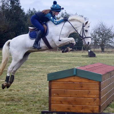 Horse and rider jumping cross country fence