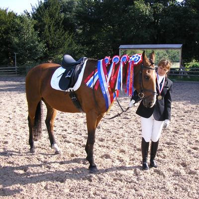 Horse and rider with British Dressage Championship Rosettes